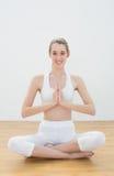 Calme a la mujer entonada que se sienta en la posición de loto en pasillo de deportes Imagen de archivo libre de regalías