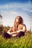 Calme a la mujer que se relaja en campo de hierba asoleado foto de archivo