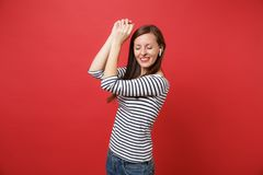 Calmed young woman with closed eyes in striped clothes with wireless earphones rising hands, listening music isolated on. Red background. People sincere royalty free stock photography