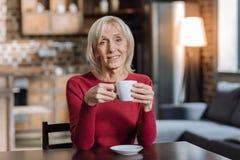 Calmez la femme âgée s'asseyant avec une tasse blanche dans des ses mains Photographie stock libre de droits