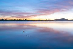 Calming effect of long exposure. Sunrise over bay in pink and blue hues stock images