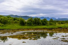 Scandinavian Ocean Bliss. A calming Ocean Vista with a gorgeous cloudscape and rocky island formations in the background and tide pools in the foreground Stock Photos
