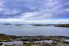 Scandinavian Ocean Bliss. A calming Ocean Vista with a gorgeous cloudscape and rocky island formations in the background and tide pools in the foreground Royalty Free Stock Photo