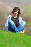 Calmness. Young woman relaxing on a green field stock photography