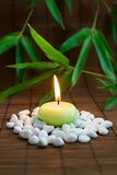 Calmness and harmony. Flaming candle, white stones and bamboo leaves. Symbolizing meditation and inner harmony Royalty Free Stock Images