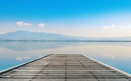 Calmness Lake with mountain in sunset. Calmness Lake with mountain and wooden plank pier in sunset Stock Photo