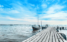 Calmness lake shore with small fishing boat Stock Photos