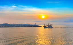 Calmness seashore with fishing boat over the sea in sunrise. Calmness seashore with fishing boat over the sea in beautiful morning sunrise Stock Image