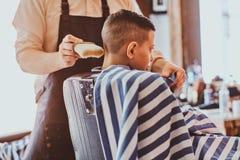 Calmo pouco menino de escola est? preparando-se para a escola no barbeiro na moda fotografia de stock royalty free