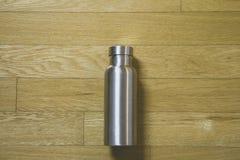 Calor - isolando engarrafe a garrafa Manter-morna de aço inoxidável na tabela de madeira fotos de stock