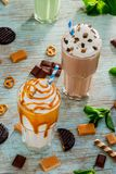 Caloric cocktails for everyone thirsty. Vanilla and cocoa milkshake with a lot of caramel, whipped topping and pieces of cookies. Toffee, salty cracknel stock photography