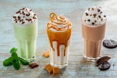 Caloric drinks for hot weather. Cold milkshakes as a traditional American cocktails with milk, ice cream and various ingredients as chocolate, vanilla, mint stock image