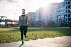 Calorie brucianti della donna adatta dei giovani con il salto alterno Fotografia Stock Libera da Diritti