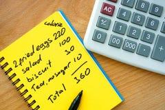 Calorie het tellen op een document met calculator stock foto