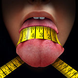 Calorie Restriction. Concept as a tape measure wrapped tight around a human tongue as a fasting diet or dieting symbol for anorexia or dietary control Royalty Free Stock Images