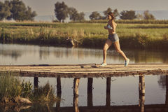Calories burning. Happy athletic young woman in summer sportswear running, sprinting on a rustic wooden footbridge across a pond at sunrise. Calories burning stock photos