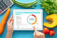 Free Calories Counting , Diet , Food Control And Weight Loss Concept. Woman Using Calorie Counter Application On Tablet At Dining Table Stock Photography - 154675362