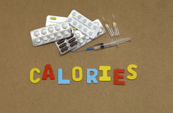 Calories. Drugs and the inscription letters on the board Royalty Free Stock Photography