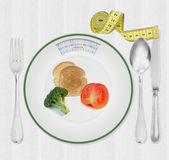 Calories scale plate with diet food. Calories scale plate with broccoli, bread and tomato royalty free stock image