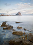 Calpe Seascape. Beautiful seascape taken in the city of Calpe (Spain) with some rocks on the foreground and the buildings of the town and the famous mountain Royalty Free Stock Photos