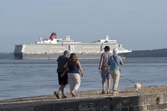Calshot Hampshire UK, A passing cruise ship and people walking on the beach. Holidaymakers walking at Calshot Spit on Southampton Water southern England UK with royalty free stock photos
