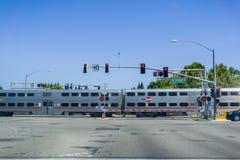 Caltrain die bij een straatverbinding dichtbij een woonbuurt in Sunnyvale kruisen Royalty-vrije Stock Foto's
