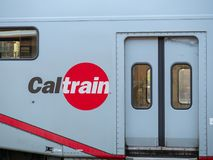 Caltrain logo on display on side of train next to passenger door royalty free stock images