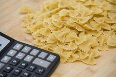 Calulator con pasta su fondo di legno, calorie Fotografia Stock