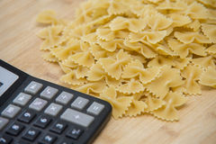 Calulator with pasta on wooden background, calories Stock Photography