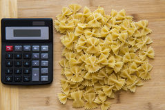 Calulator with pasta on wooden background, calories Royalty Free Stock Photo