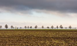 Calvario con gli alberi vicino al campo di agricoltura Prato e campagna in repubblica Ceca Nuvole temporalesche sopra la costruzi Fotografie Stock Libere da Diritti