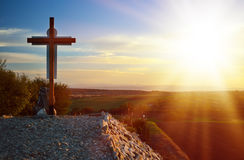 Calvary cross. Lone Christian cross on stony Hill, against the backdrop of fields and mountains. Bright Sunny rays Stock Image