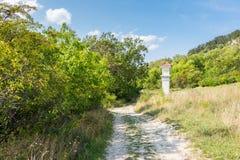 Calvary dichtbij de weg met bomen en struiken Blauwe de zomerhemel royalty-vrije stock foto's
