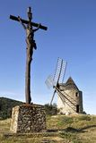 Calvary and wind-mill. Calvary in the foreground and mind-will on the blue sky background Stock Photo