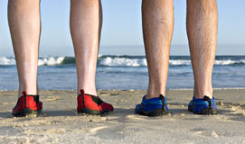 Calves and feet on the beach. The calves and feet with shoes of two men on the beach in late afternoon sunlight stock photos