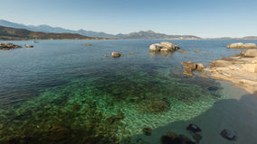Calvi bay in Corsica with shallow water and rocks Stock Photography
