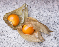 An calyx open, exposing the ripe fruit of physalis peruviana. On a slate of marble Stock Photo