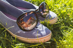 Calza las zapatillas de deporte en la hierba con las gafas de sol, la relajación del verano y el concepto de la rotura Imagen de archivo