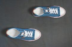 Calza las zapatillas de deporte en un paño oscuro bajo la forma de pista que camina Imagenes de archivo