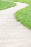 Calzada concreta e hierba verde imagen de archivo