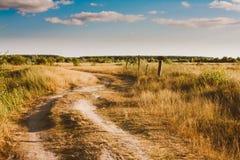 Calzada de la trayectoria del camino del campo de la bobina a través de Autumn Field Meadow Fotografía de archivo libre de regalías