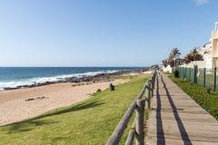 Calzada de madera contra el cielo nublado azul en la playa de Ballito Foto de archivo