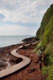 Calzada de madera de la curva por el mar Fotos de archivo