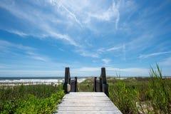 Calzada de madera a la playa debajo de un cielo brillante del verano fotografía de archivo libre de regalías
