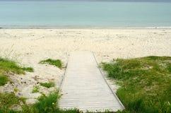 Calzada de madera que lleva abajo a la arena blanca de la playa del verano Foto de archivo libre de regalías