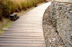 Calzada de madera y pared de piedra Foto de archivo libre de regalías