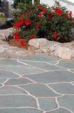 Calzada de piedra con las flores imágenes de archivo libres de regalías