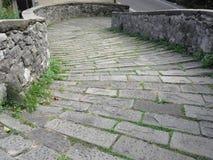 Calzada de piedra de la pendiente del puente medieval conocida como Ponte del Diavolo en Borgo un Mozzano, Italia Fotografía de archivo libre de regalías