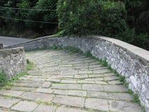 Calzada de piedra de la pendiente del puente medieval conocida como Ponte del Diavolo en Borgo un Mozzano, Italia Imágenes de archivo libres de regalías
