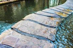 Calzada de piedra sobre el agua con las tiras de metal entre las rocas y el agua que salpica para arriba en una sección imágenes de archivo libres de regalías